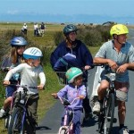 Family cycling by the coast